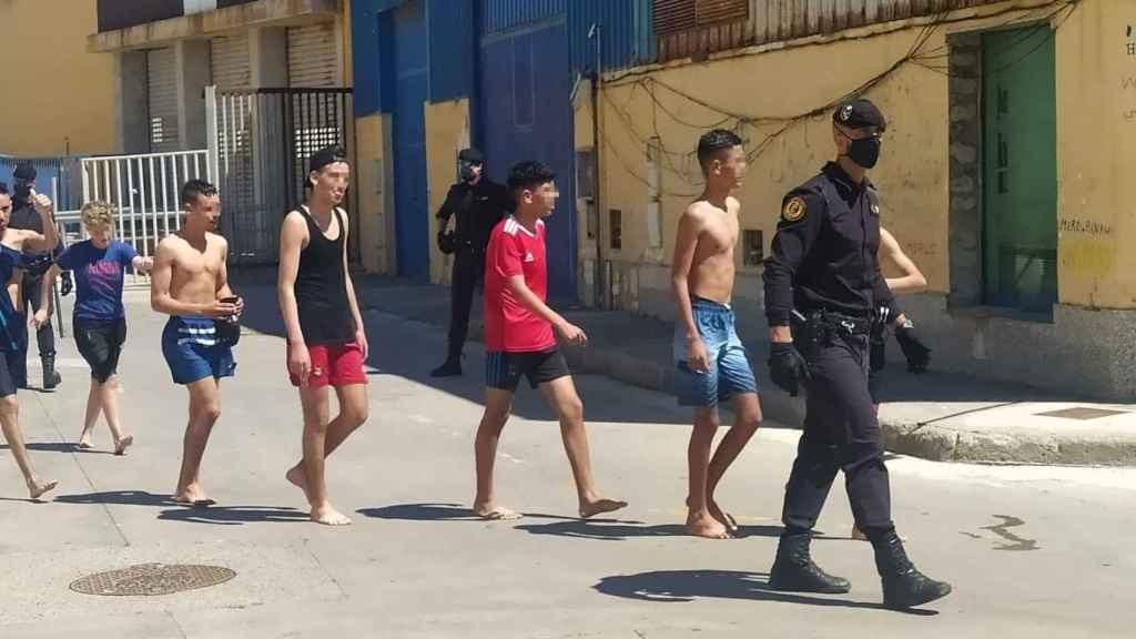 Un agente de la policía nacional junto a varios de los inmigrantes que han llegado a nado este lunes a Ceuta.