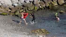 Un grupo de siete inmigrantes a su llegada esta mañana a Ceuta por el espigón sur del Tarajal.