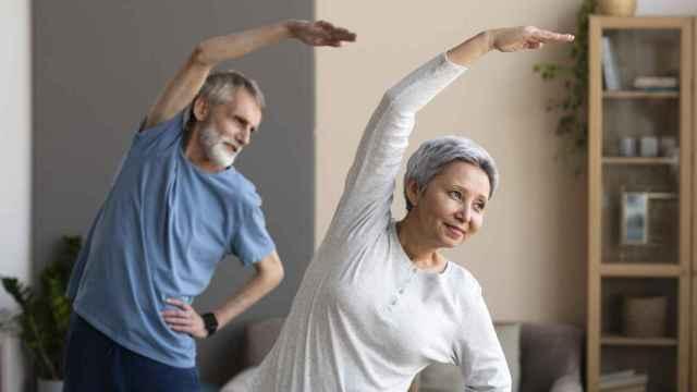 Pareja de personas mayores entrenando en casa.