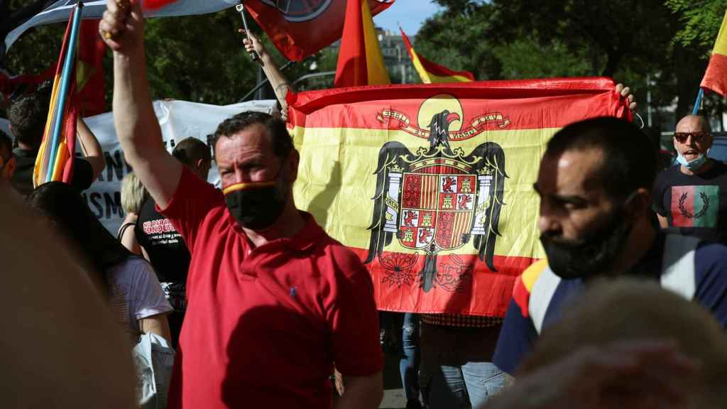 Varias personas con una bandera franquista participan en una concentración frente a la Embajada de Marruecos en Madrid.