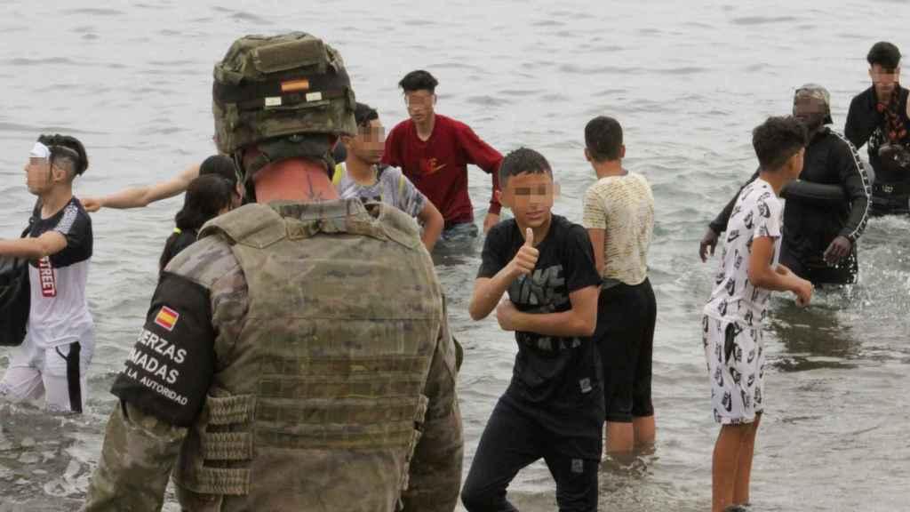 Un militar observa a un grupo de menores marroquíes en las playas de Ceuta.