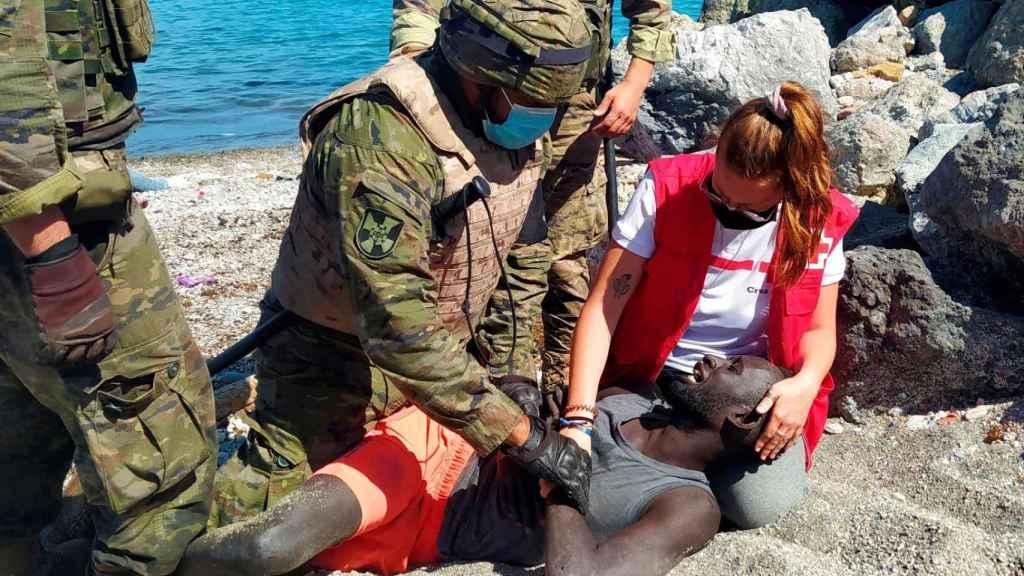 Luna, junto a miembros del Ejército, ayuda a un inmigrante que ha logrado cruzar uno de los espigones fronterizos de Ceuta este martes.