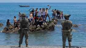 Un grupo de inmigrantes marroquíes, ante los militares españoles que patrullan la frontera de Ceuta.