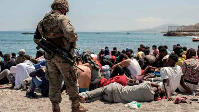 Inmigrantes sentados en la playa de El Tarajal, de Ceuta, ante un soldado español.