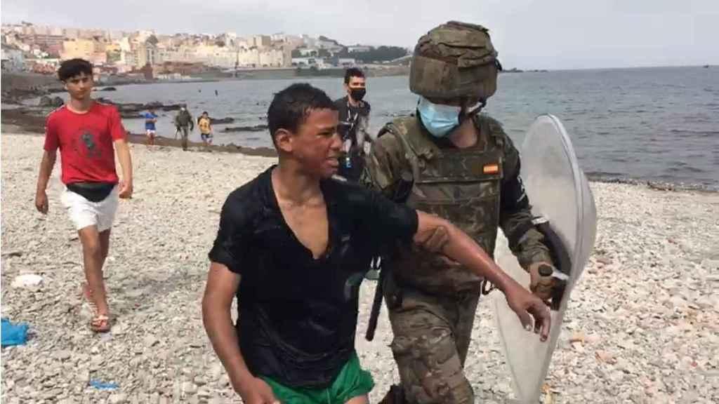 Un adolescente llora después de que un soldado español lo recogiera en la playa en la tarde de este miércoles.