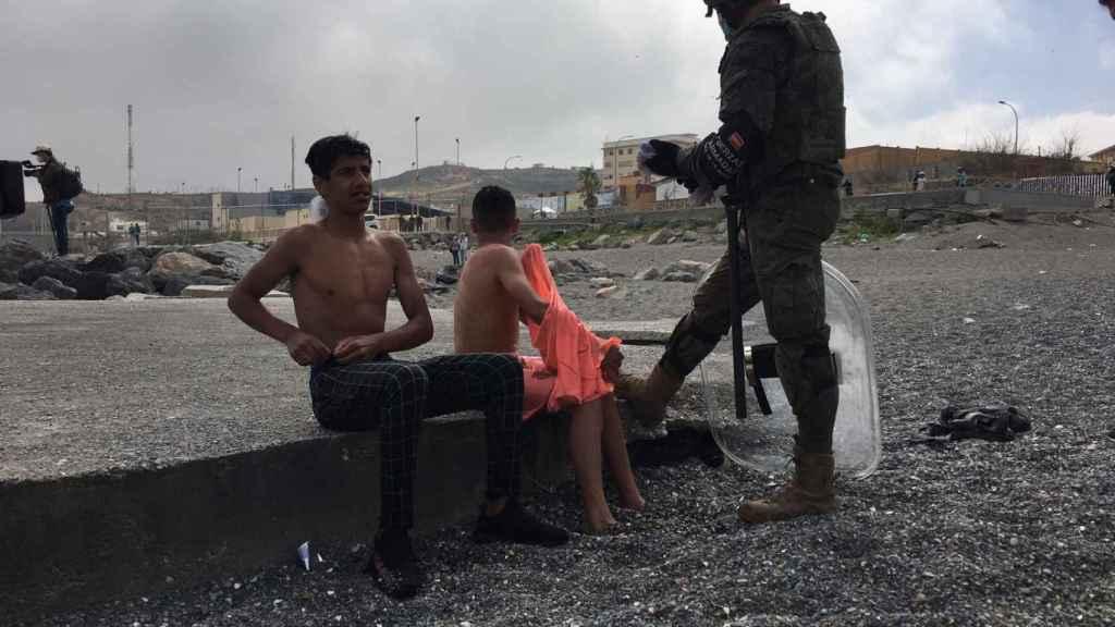 Un militar habla con dos menores después de sacarlos del agua en la playa de El Tarajal.