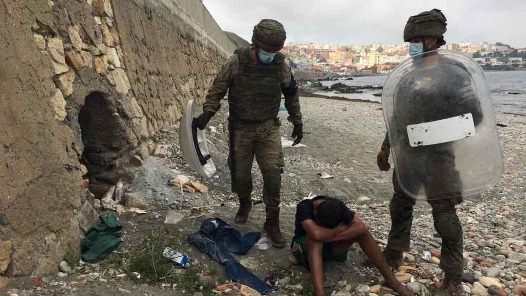 Dos militares españoles atienden a un joven marroquí recién llegado a Ceuta.