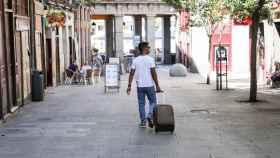 Un turista pasea con una maleta por el centro de Madrid.