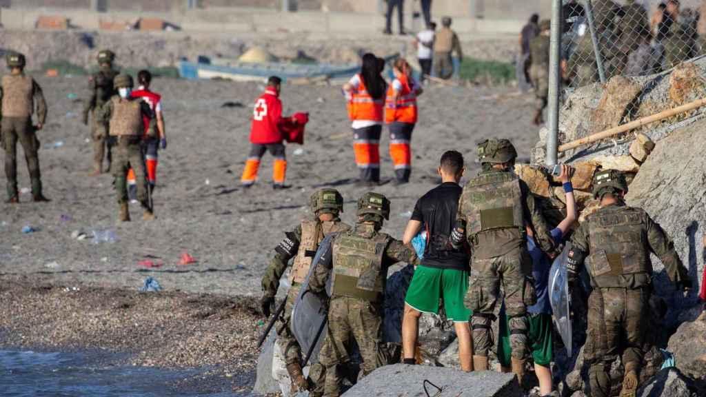 Miembros del Ejército ayudan a varios inmigrantes a su llegada a la playa de El Tarajal. Efe