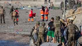 Miembros del Ejército ayudan a varios inmigrantes a su llegada a la playa de El Tarajal.