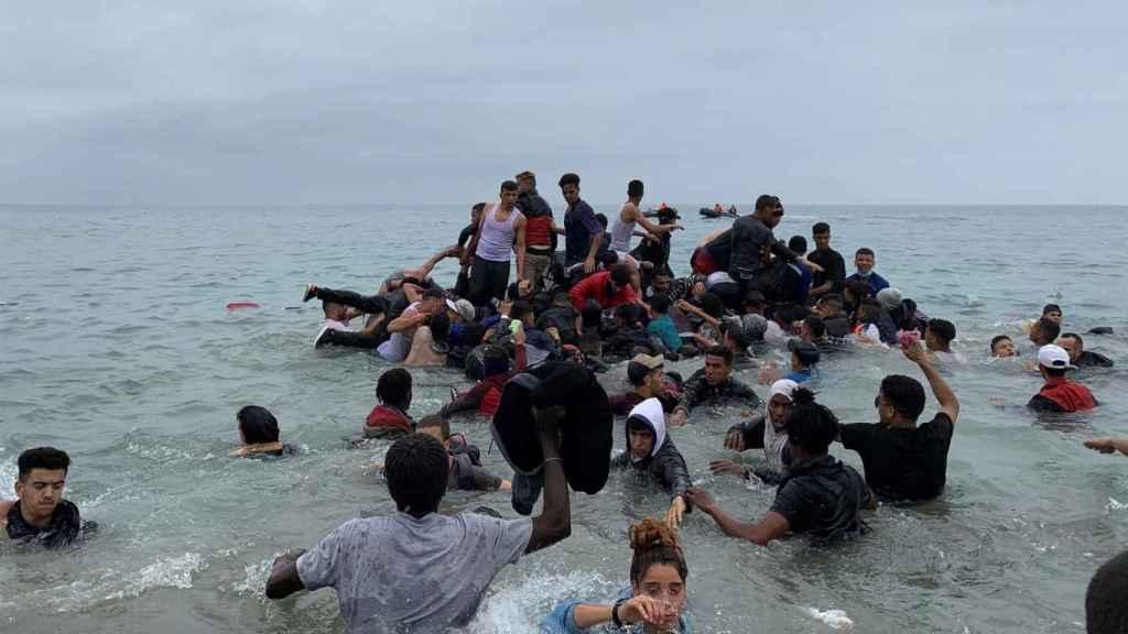 Menores inmigrantes entran a la playa de El Tarajal en Ceuta desde Marruecos.