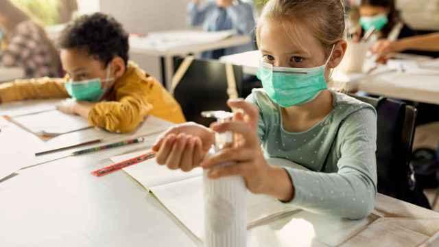 Dos alumnos utilizan mascarillas y gel hidroalcohólico en el aula.