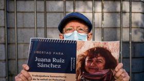 Un simpatizante de Juana Ruiz sostiene su foto en la manifestación del 29 de abril frente a la embajada de Israel en Madrid.