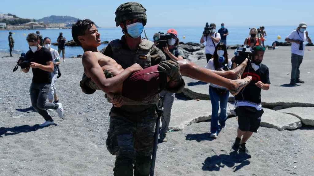 Un militar traslada en brazos a un menor llegado a las costas de Ceuta a nado.