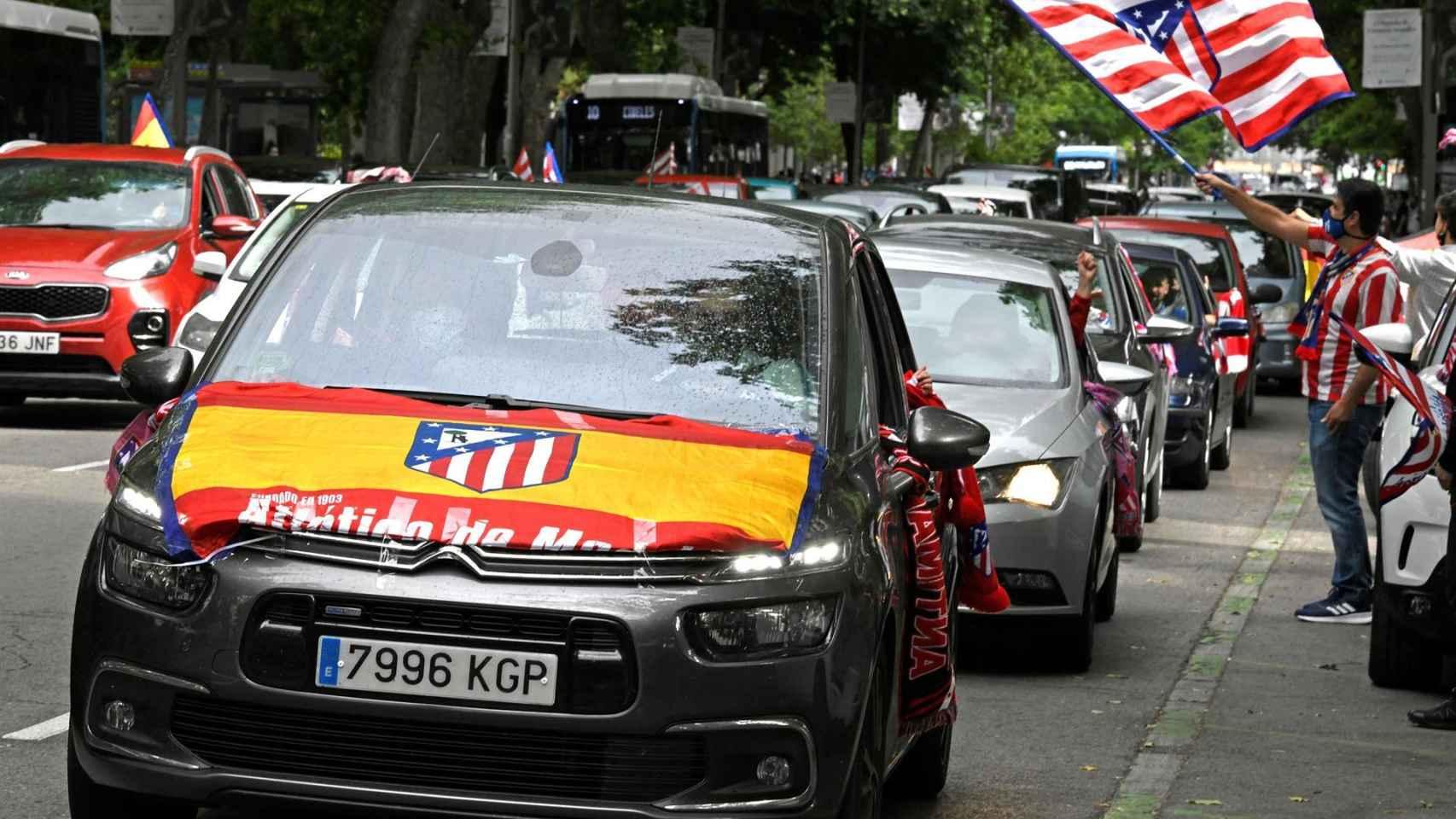 Un coche luce la bandera de España con el escudo del Atlético