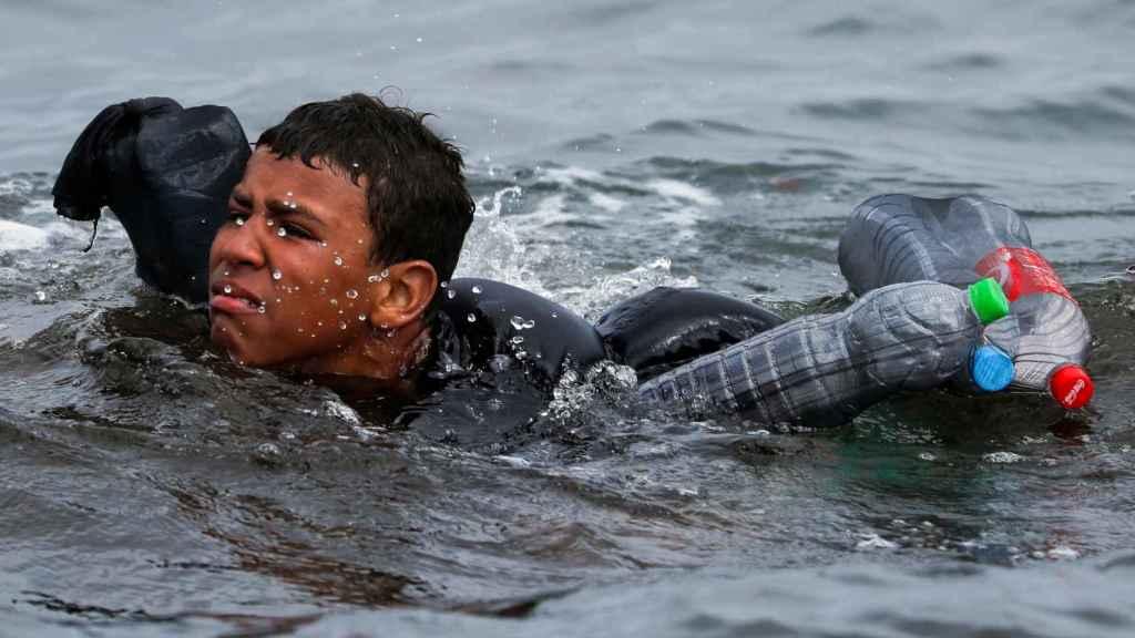 Un menor marroquí trata de alcanzar la playa de Ceuta