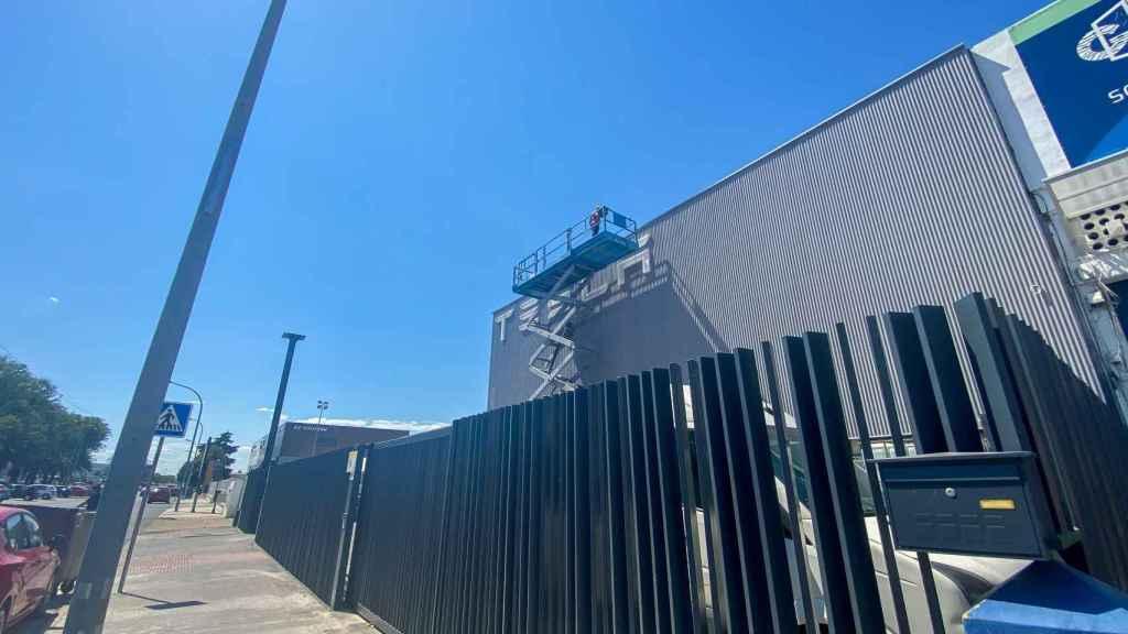 Operarios ultiman la fachada del primer centro de servicio de Tesla en Sevilla.