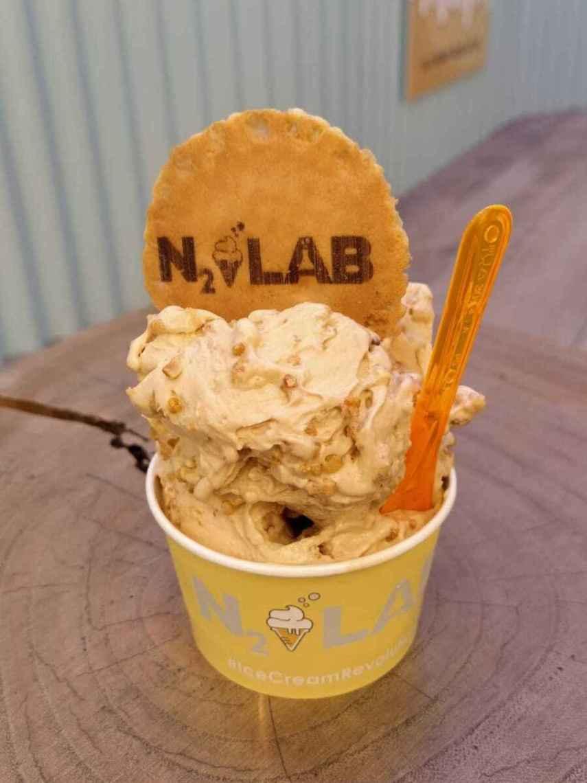 La tarrina de helado de N2 Lab, que contiene una bola de helado de caramelo con un 'topping'.
