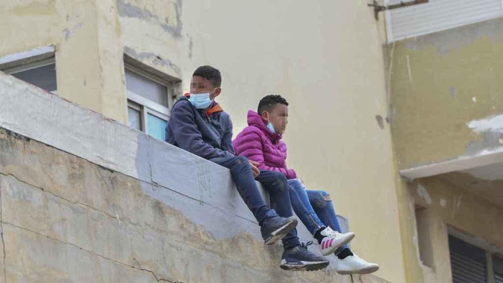 Dos niños sentados sobre un muro en la nave de primera acogida del polígono del Tarajal, en Ceuta. EP