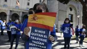 Una mujer con una pancarta y una bandera en la concentración contra el recorte de caudal del Trasvase Tajo-Segura .
