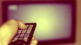 Un usuario apunta a una televisión con un mando a distancia.
