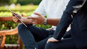 Dos ejecutivos en una reunión al aire libre.