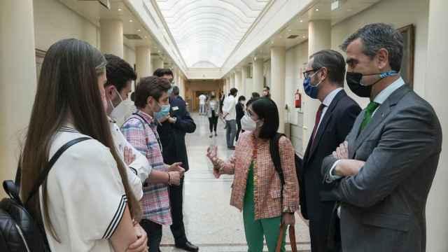 La ministra de Sanidad junto con algunos MIR en los pasillos del Senado, acompañados de los portavoces de PP, Javier Maroto y Antonio Román.