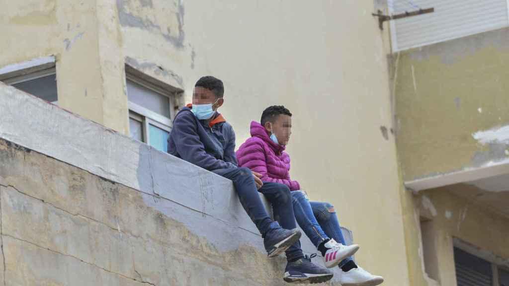 Dos menores encaramados a un muro en una de las naves de El Tarajal.