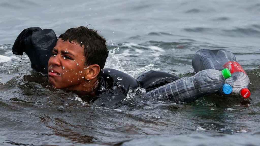 Un menor trata de llegar a nado a España por el espigón de El Tarajal.
