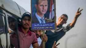 Un hombre con una pancarta de Bashar Al-Assad.