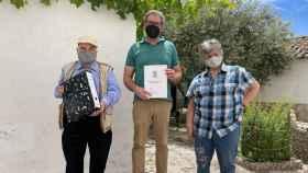 El concejal de cultura Josué López recoge la colección, de manos de Ángel y Sagrario en el patio de su casa de Santa Olalla.