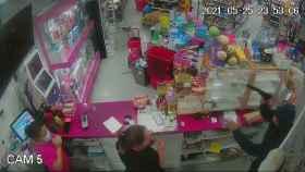 Uno de los atracadores encañonando a las dos empleadas.
