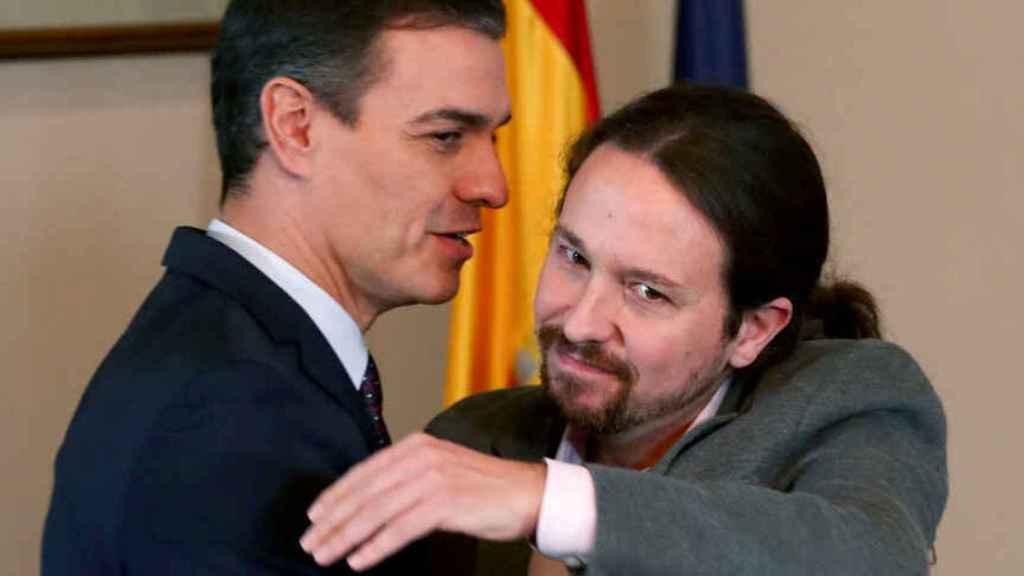 Pedro Sánchez mira de reojo a Pablo Iglesias en el abrazo con el que sellaron su acuerdo de Gobierno de coalición. Reuters