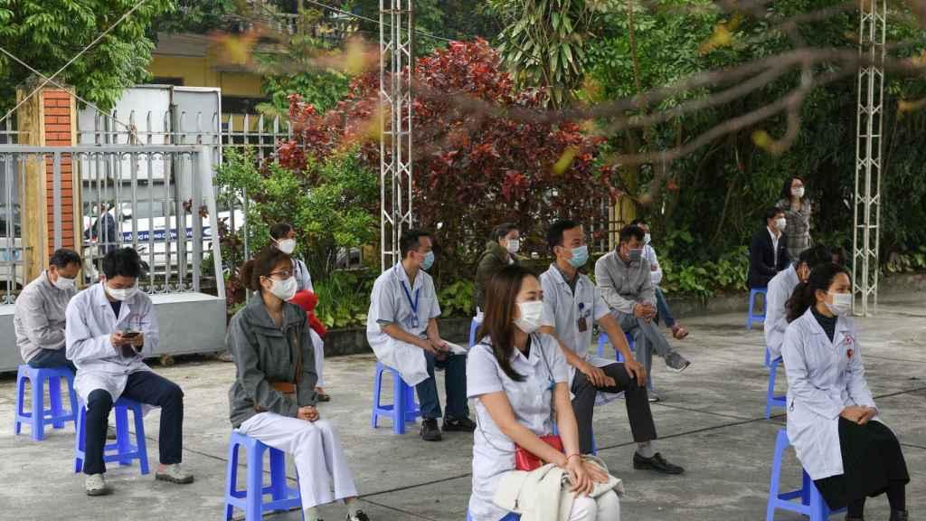 Una decena de personas esperan para recibir la vacuna en Hai Duong.