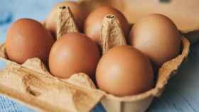 Una caja con media docena de huevos.