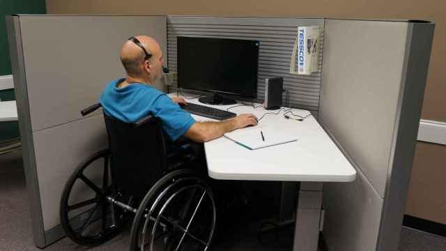 Una persona con movilidad reducida, frente a una pantalla de ordenador en su puesto de trabajo. FOTO: Pixabay.