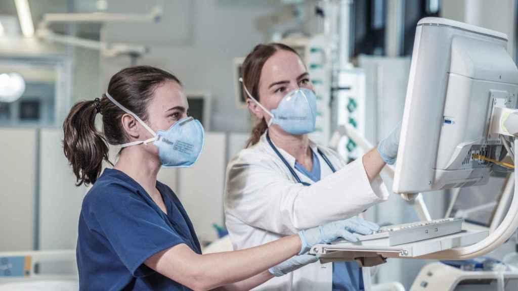 Dos sanitarias manipulando un equipo médico.