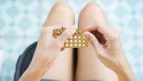 Una mujer con unas pastillas anticonceptivas.