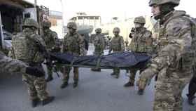 Soldados británicos trasladan el cadáver de una víctima del atentado de 2015 en la embajada española en Kabul.