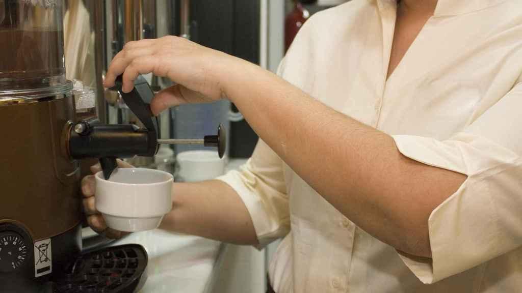 El empleado de un establecimiento sirviendo un café.