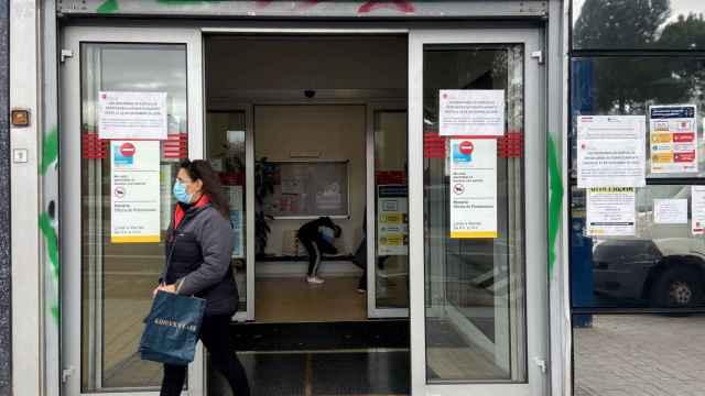 Una mujer, delante de una oficina de empleo.