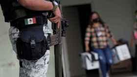 Un agente de la Guardia Nacional escolta a una mujer con urnas en el Estado de Nuevo León.