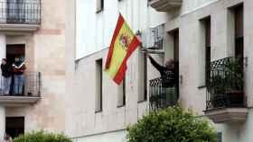 Un ciudadano ondea la bandera española desde su ventana.