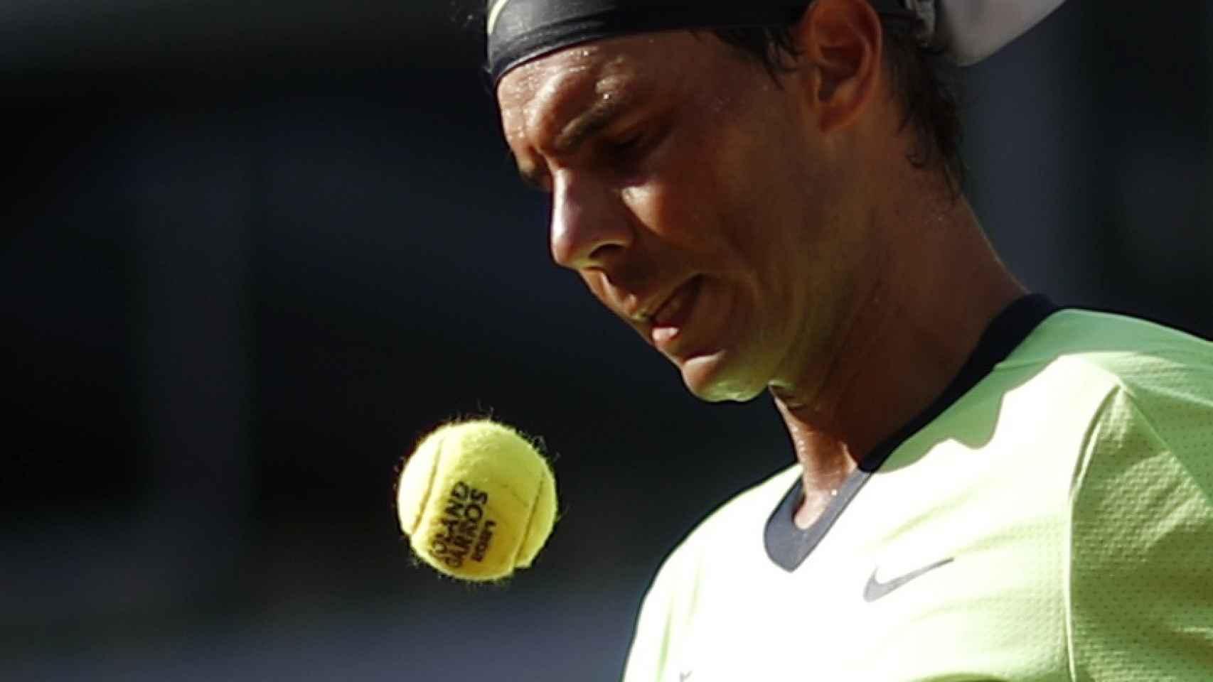 Rafa Nadal, escogiendo pelota antes de sacar en Roland Garros 2021