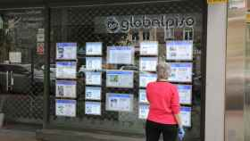 Una mujer echa un vistazo a las ofertas de una agencia inmobiliaria.