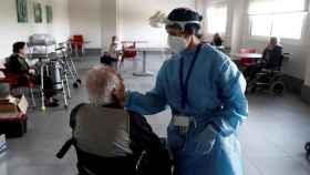 Una profesional realiza pruebas PCR a un hombre en una residencia de ancianos.