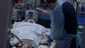 Un sanitario atiende a una persona con coronavirus.