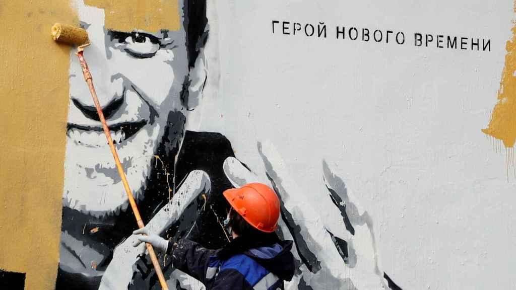 Un trabajador borra un mural de Navalny.