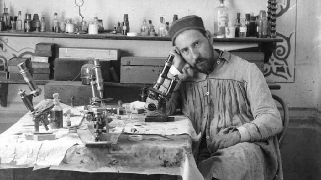 Ramón y Cajal junto a un microscopio en su despacho.