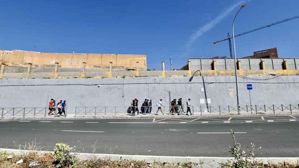 Varios migrantes procedentes de Marruecos hacen cola en las puertas de la frontera de Ceuta.